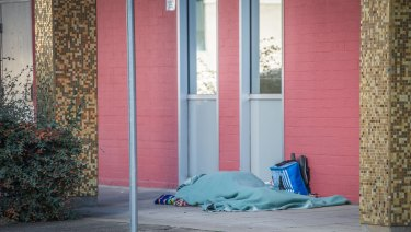A homeless person sleeps rough outside the ACT Legislative Assembly on Monday.
