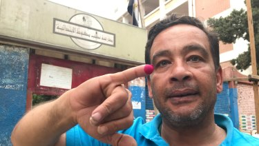 Emad Rashad shows off his inked finger as proof of voting.