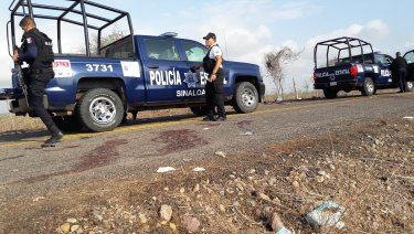 Police officers guard a crime scene after authorities reported a gun battle with armed men near the beach resort of Mazatlan, Mexico in July.