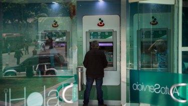 A customer uses a Banesco ATM in Venezuela.