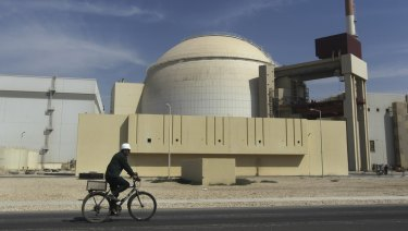 A worker rides a bike in front of the reactor building of the Bushehr nuclear power plant, just outside the southern city of Bushehr, Iran.