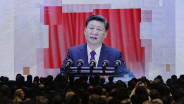 A screen shows Chinese President Xi Jinping during a symposium in Hong Kong.