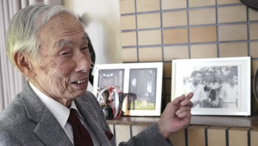 Kazuo Oda, a long-time tennis friend of Emperor Akihito, points to a photograph of him with the then crown price Akihito and Michiko Shoda, who became Empress.