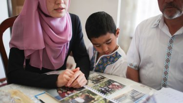 In Adelaide, a five-year-old boy views photos of relatives that have gone missing or are in Uighur internment camps.