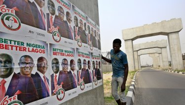 A man looks at campaign posters, near mono rail line pillars under construction in Lagos, Nigeria.