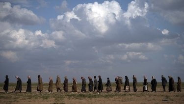 Men on their way to be screened after being evacuated from former Islamic State territory near Baghouz, Syria.