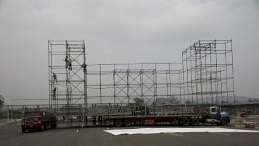 "Workers build a stage for the upcoming pro-government concert coined ""Hands Off Venezuela"" on the Venezuelan side of Tienditas International Bridge that leads to Colombia."
