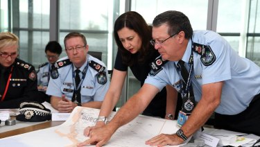 Queensland Premier Annastacia Palaszczuk (centre) is briefed by Police Commissioner Ian Stewart (right) on the floods situation in the state's north in March 2018.