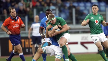 Tough grind: Ireland's John Ryan hits the line during the 26-16 Six Nations victory over Italy in Rome.