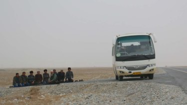 Uighur men stop their bus on the roadside to pray on a highway leading into Hotan in Xinjiang.
