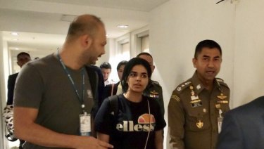 Chief of Immigration Police, Major General Surachate Hakparn (right) walks with Rahaf Mohammed al-Qunun as she leaves Suvarnabhumi Airport in Bangkok  last month.