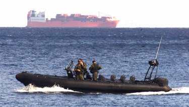 Boat-borne politics: An Australian Army vessel patrols the waters near Norwegian freighter Tampa in 2001.