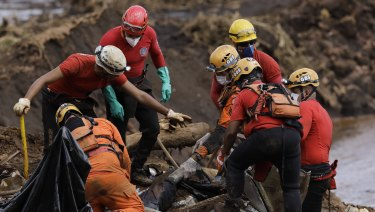 Firefighters pull a body from the mud days after the Vale mining company's dam collapsed in Brumadinho, Brazil.
