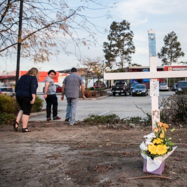 A cross outside the Hungry Jack's car park in southwest Sydney marks the spot where police shot Courtney Topic.