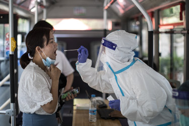 A medical worker takes samples during a mass COVID-19 test in a residential block in Wuhan.