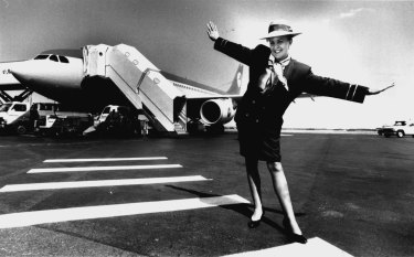 Flight attendant Helen Corney pictured near a Compass Airways jet at Brisbane Airport