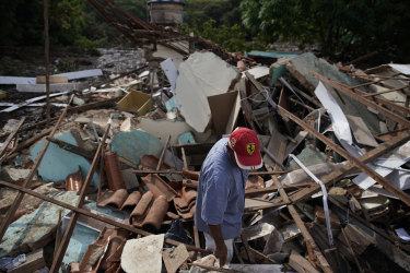 A man stands in the debris of his home that was destroyed after the collapse.