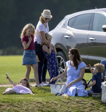 The Duchess of Cambridge, second right, sits with Prince George and Princess Charlotte as she talks to Autumn Phillips and her children, Savannah and Isla, as they watch Prince William take part in a charity polo event on Sunday.