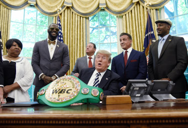 This image, in which Donald Trump signs an executive order granting a posthumous pardon for boxer Jack Johnson while Sylvester Stallone watches on, briefly features in the video.