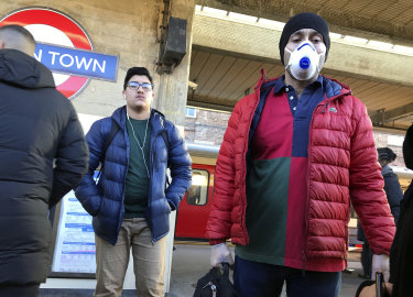 A commuter wears a face mask while waiting to catch the tube in London