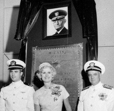 From left, US Navy Lieutenant Commander John McCain III and his parents, Roberta McCain and Rear Admiral John McCain jnr, stand in front of a plaque with an image of his grandfather, Admiral John McCain, at the Naval Air Station Meridian McCain Field in Mississippi, in 1961.