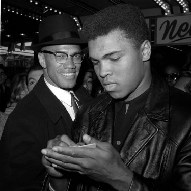 World heavyweight boxing champion Muhammad Ali, right, is shown with black muslim leader Malcolm X outside the Trans-Lux Newsreel Theater in New York, after viewing the screening of a film about Ali's title fight with Sonny Liston, in this March 1, 1964 file photo.