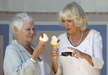 The Duchess of Cornwall Camilla enjoys an ice cream with Dame Judi Dench, left, as she arrives at Queen Victoria's private beach, next to the monarch's holiday home in East Cowes on the Isle of Wight, Tuesday July 24, 2018.