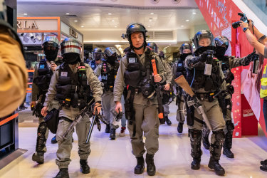 Riot police secure an area during a demonstration in a shopping mall.