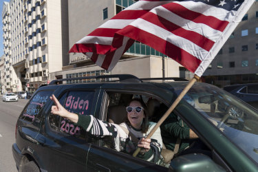 A Biden supporter cheers while driving past a Trump rally protesting the election results.