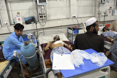 Wounded Afghans lie on a bed at a hospital after a bomb attack in the city of Jalalabad.