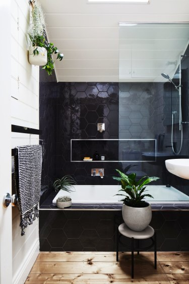 A skylight floods the monochromatic upstairs bathroom. The plant stand and hanging basket were designed by Jacqui and business partner Alana Langan for Ivy Muse.