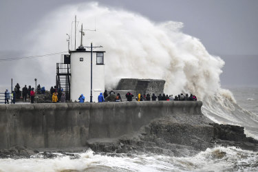Waves and rough seas pound against the harbour wall at Porthcawl in Wales.
