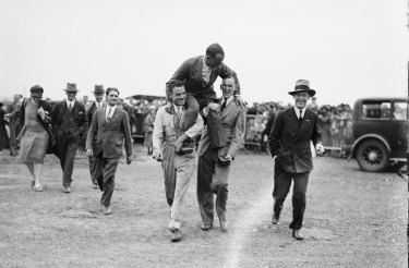 Aviator Captain Matthews being carried on the shoulders of two men after his arrival at Mascot on October 27, 1930.