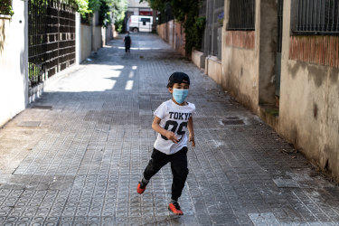 Toni Roses runs on the street outside his house in Barcelona, Spain.