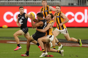 Gotcha: Hawthorn's Jack Scrimshaw gets his hands on Carlton's Jack Martin.