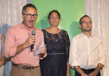 Standing with candidate Alex Bhathal and deputy leader Adam Bandt, Greens leader Richard Di Natale concedes defeat in Batman on Saturday,