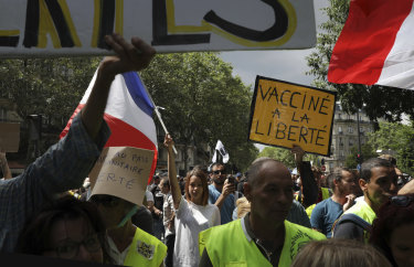 """A protestor holds a sign which reads """"vaccine to freedom"""" during a demonstration in Paris on Saturday."""