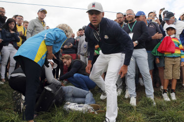 US golfer Brooks Koepka offers a golf glove to a spectator he injured when his ball strike hit her.