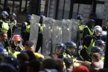 British police officers in riot gear scuffle with members of far-right groups in London.