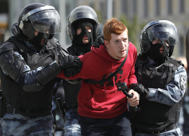Police officers detain a protestor during an unsanctioned rally.