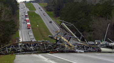 A fallen telephone tower lies across US Route 280 highway in Lee County, Alabama after a tornado struck on  Sunday.