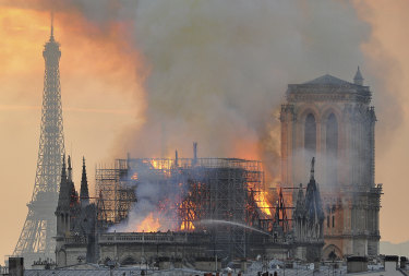 Flames and smoke rise from the blaze after the spire toppled over on Notre Dame.