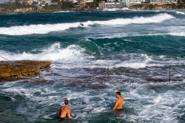 People enjoying a cold swim and watching the big surf at Bondi Beach in winter.