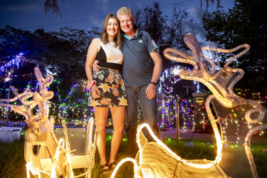 Lindsay McAlister, left, with her father Scott McAlister at their house in Reid, lit up for Christmas.