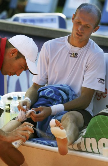 Nikolay Davydenko, right, receives treatment on his foot during his second round match with Martin Vassallo Arguello, of Argentina, at the Prokom Open in Sopot, Poland in 2007.