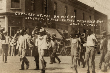 A group of Black men are marched past the corner of 2nd and Main Streets in Tulsa, Okla., under armed guard during the Tulsa Race Massacre on June 1, 1921.