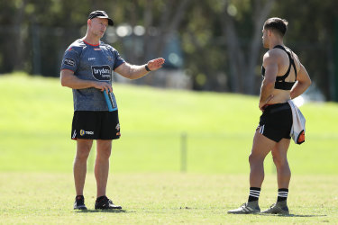 Michael Maguire talks to a Tigers player on the training paddock shortly before the NRL was suspended.