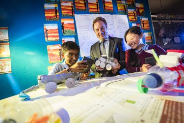 Years 4 students at St Christopher's Primary School, Therese and Naethan, work on their science projects with principal Shane Davoren.