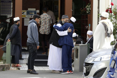 Muslim men embrace as they leave the Al Noor mosque in Christchurch, New Zealand.