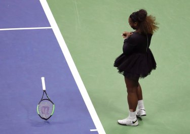 Serena Williams smashes her racket.